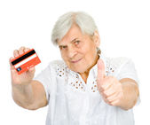 Closeup of old woman holding credit card with thumbs up — Stock Photo