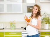 Pregnant woman in kitchen eating a salad smiling.looking at camera — Stock Photo