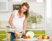 Pregnant woman in kitchen making a salad — Stock Photo