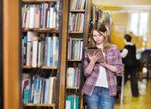 νεαρός φοιτητής εστιασμένη που χρησιμοποιώντας έναν υπολογιστή δισκίο σε μια βιβλιοθήκη — Φωτογραφία Αρχείου