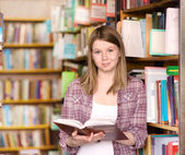 Happy girl with book at the library — Foto Stock