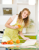 Pregnant mother preparing food in kitchen. Beautiful young caucasian woman reading cooking recipe while making salad. Looking at camera — Stock Photo