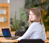 Young student using computer in a library — Stock Photo