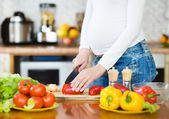 Close up pregnant woman with knife on kitchen cuts vegetables — Stock Photo