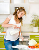 Beautiful pregnant mother pour out milk into glass on the house kitchen — Stock Photo