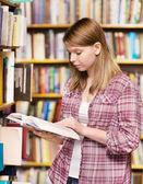 Estudiante pensativo en la biblioteca rodeada de libros — Foto de Stock