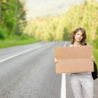 Pretty young woman tourist hitchhiking along a road. — Stock Photo