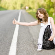 Beautiful young woman hitchhiking along a road — Stock Photo