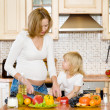 Stock Photo: Pregnant mother and daughter in kitchen