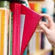 Stock Photo: Closeup hand selecting book from bookshelf