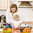 Pregnant mother and daughter in kitchen - Photo