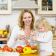 Mother and daughter eating vegetables salad in kitchen — Stock Photo