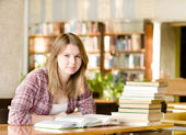 Happy girl with books at the library. looking at camera — Stockfoto