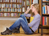 Sad student in library — Stock Photo