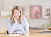 Ganska unga collegestudent i ett bibliotek titta på kameran — Stockfoto