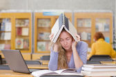 Sad student with laptop working in library — Foto de Stock