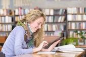 Jeune étudiant ciblé à l'aide d'une tablette pc dans une bibliothèque — Photo