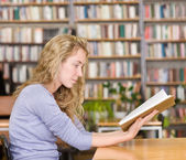 Female student reads the book in library — Stock Photo