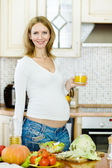 Pregnant woman with glass of juice in the house kitchen looking at camera — Stock Photo