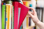 Closeup hand selecting book from a bookshelf — 图库照片