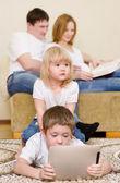 Děti pomocí tabletový počítač u rodičů v domácnosti — Stock fotografie