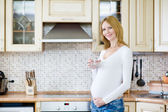 Attractive pregnant woman holding a glass of clean water while standing in the kitchen and looking at camera — Stock Photo