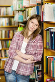 Happy girl at the library. looking at camera — Stok fotoğraf