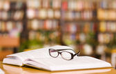 Book and glasses on table in library — Foto Stock
