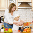 Pregnant mother and daughter in kitchen — Stock Photo
