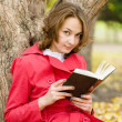 Young woman reading a book in the autumn park — Stock Photo