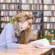 Pretty young college student in a library — Stock Photo #20256817