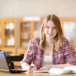 Pretty female student with laptop and books working in a high school library — Stock Photo