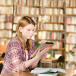 Stock Photo: Girl with electronic pad in library