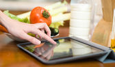 Hands typing on tablet computer in kitchen — Stock Photo