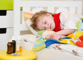 The sick child sleeps on a bed — Stock Photo