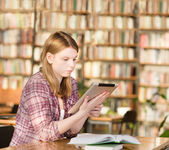 Girl with electronic pad in library — Stok fotoğraf