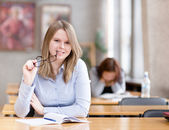 Pretty young college student in a library. looking at camera — Stock Photo