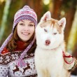 Closeup teen girl embracing cute dog in winter park — Stock Photo #21232669