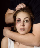 Domestic violence woman being abused and strangled by strong man. on dark background — Stock Photo