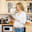 Pregnant woman using a tablet computer in kitchen. — Stock Photo