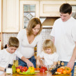 The happy family makes a dinner in kitchen — Stok fotoğraf