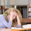 Sad student working in library — Stock Photo #21882857
