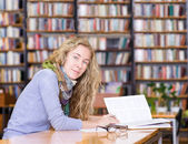 Female student reads the book in library — Foto Stock