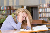 Sad student working in library — Stock Photo