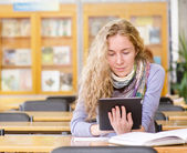 Student using a tablet computer in a library — Stock Photo