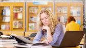 Female student with laptop working in library — Photo