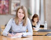 女学生在图书馆工作。看看相机 — 图库照片
