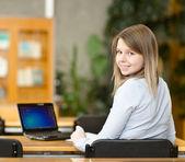 Kvinnlig student med laptop arbetar i biblioteket — Stockfoto