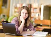 Kvinnlig student med laptop och böcker som arbetar i en gymnasiebiblioteket — Stockfoto