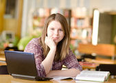 Female student with laptop and books working in a high school library — Stock Photo